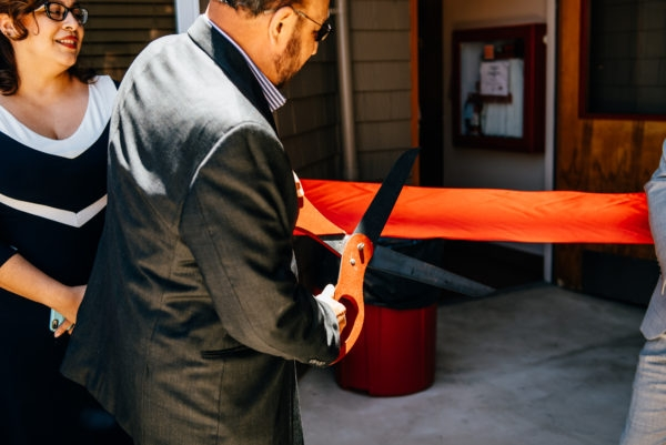 Pete Gallegos, Chair of the Mission Housing Board of Directors, cuts a ribbon to mark the reopening of Esperanza Apartments as Marcía Contreras looks on.