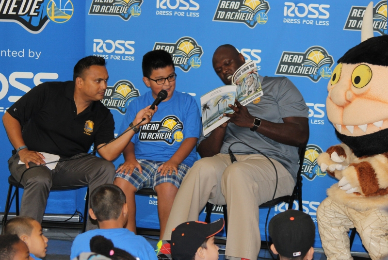 Adonal Foyle assists a student who is reading aloud at the Read to Achieve Reading Time Out