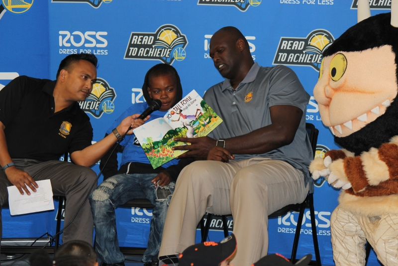 "A student reads aloud from Adonal Foyle's children's book ""Too-Tall Foyle Finds His Game"""