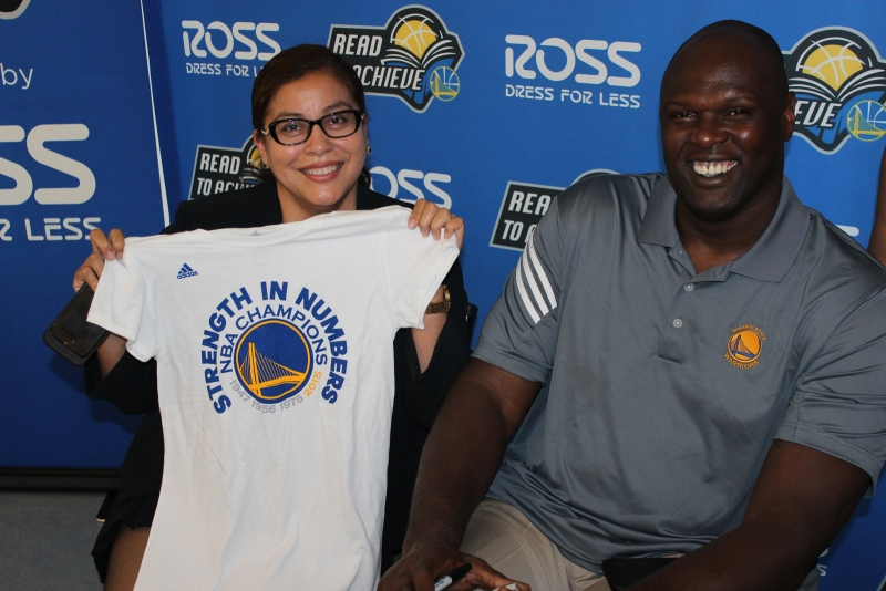 Marcía Contreras of Mission Housing receives a Warriors championship t-shirt from Warriors Adonal Foyle